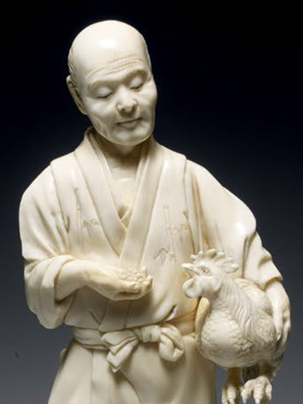 Ivory okimono of a man holding a cockerel