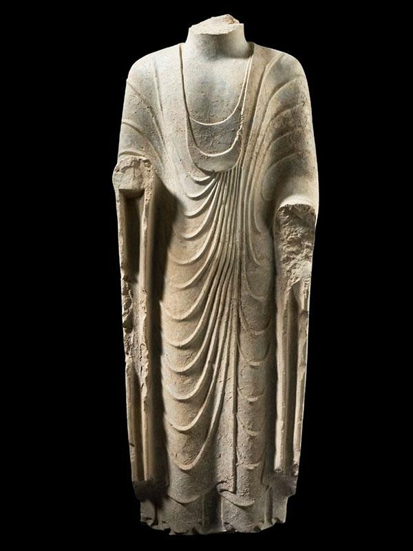 Carved limestone torso of Buddha