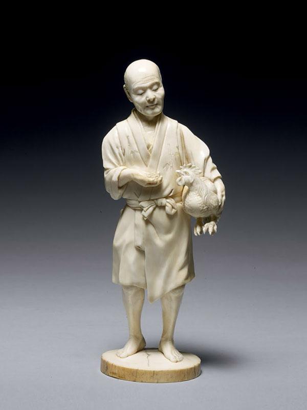 Ivory okimono of a man holding a cockerel